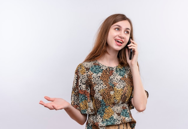 Jeune femme aux cheveux longs portant une robe colorée souriant tout en parlant au téléphone mobile debout sur un mur blanc