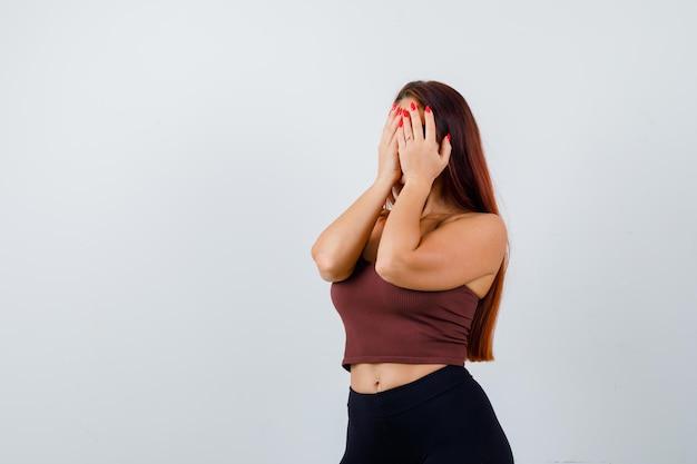 Jeune femme aux cheveux longs portant des vêtements de sport couvrant son visage