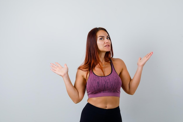 Jeune femme aux cheveux longs portant des vêtements de sport