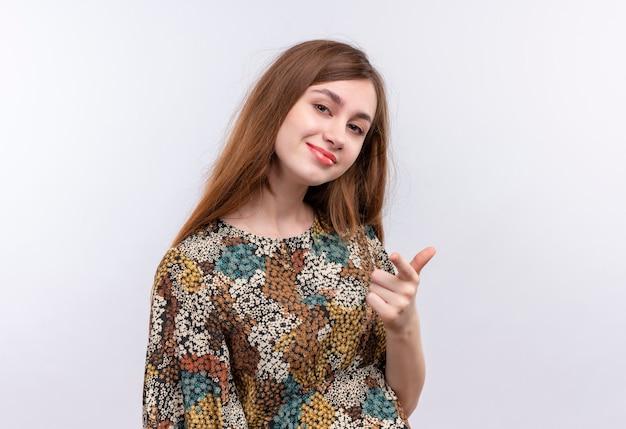 Jeune femme aux cheveux longs et robe colorée souriant confiant, pointant vers l'avant