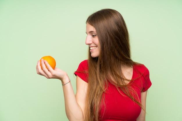 Jeune femme aux cheveux longs tenant une orange