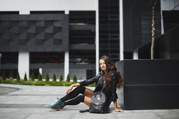 Jeune femme aux cheveux longs en veste de cuir et bas est assis sur la rue de la ville un jour d'été
