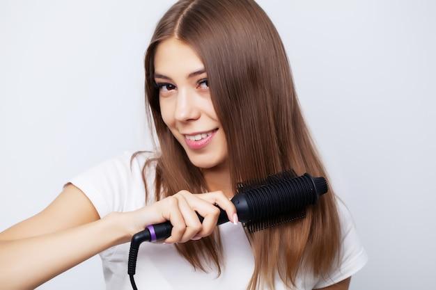 Jeune femme aux cheveux luxueux le redresse avec un fer à friser
