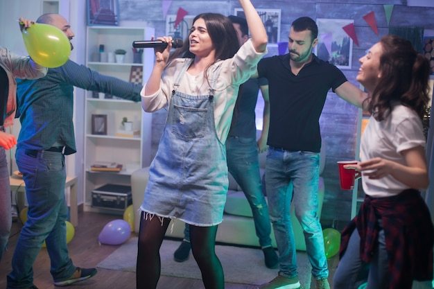Jeune femme aux cheveux noirs dansant et chantant au micro à la fête pour ses amis.