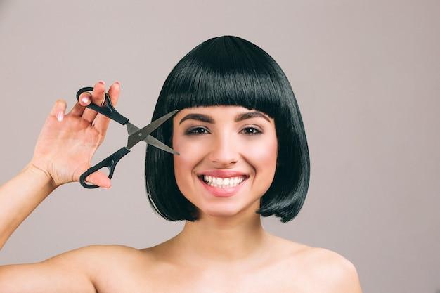 Jeune femme aux cheveux noirs posant. joyeuse belle brune avec coupe de cheveux bob souriant. regardant droit à travers des ciseaux.