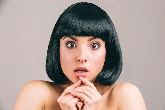 Jeune femme aux cheveux noirs posant. modèle effrayé avec coupe de cheveux bob look droit. tenir les doigts sous les lèvres.