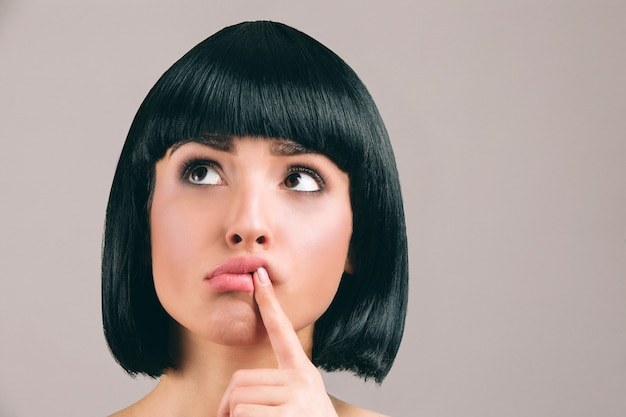 Jeune femme aux cheveux noirs posant. le modèle réfléchi étonné regarde vers la gauche et tient le doigt sur les lèvres. coupe de cheveux brune bob.