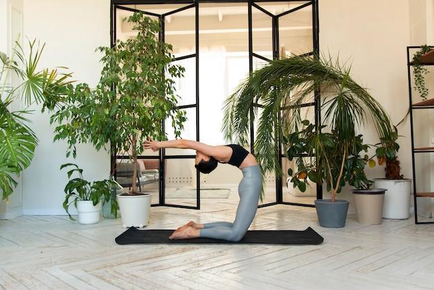 Jeune femme aux cheveux noirs pratiquant le yoga le matin chez elle près des plantes. la femme est engagée dans l'autodétermination, faisant des exercices de yoga.