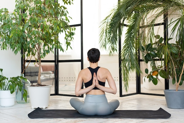 Jeune femme aux cheveux noirs pratiquant le yoga le matin à son domicile près des plantes.