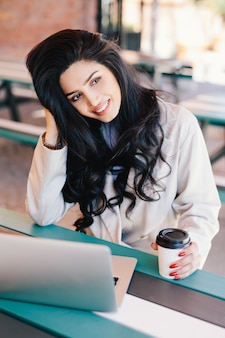 Jeune femme aux cheveux noirs tenant le café à emporter assis devant l'ordinateur portable ouvert, navigation sur internet.