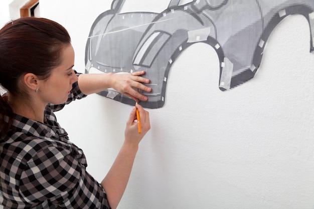 Une jeune femme aux cheveux noirs vêtue d'une chemise à carreaux dessine une grande voiture rouge dans la chambre du garçon accrochée au mur.