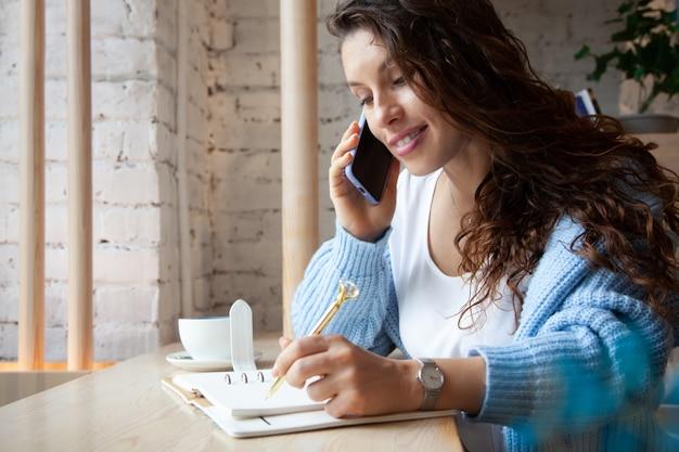 Jeune femme aux cheveux ondulés en pull tricoté bleu chaud parle au téléphone et écrit des notes tout en buvant du café latte bleu chaud et sain à base de thé aux pois papillon naturel. beauté et bien-être