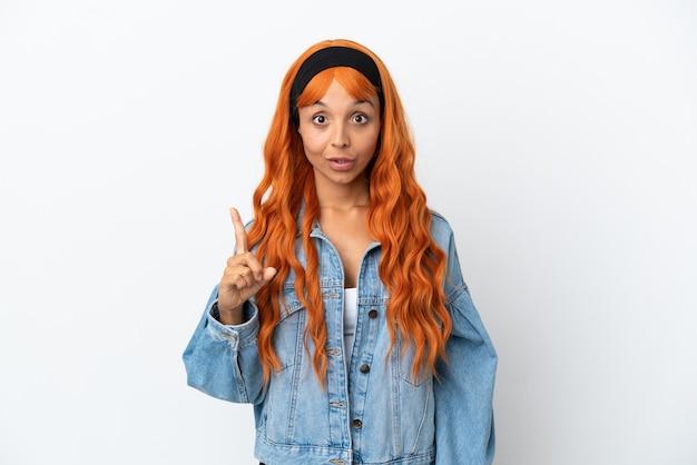 Jeune femme aux cheveux orange isolé sur fond blanc dans l'intention de réaliser la solution tout en levant un doigt vers le haut