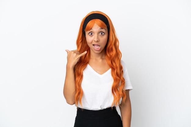 Jeune femme aux cheveux orange isolé sur fond blanc faisant le geste du téléphone. rappelle-moi signe