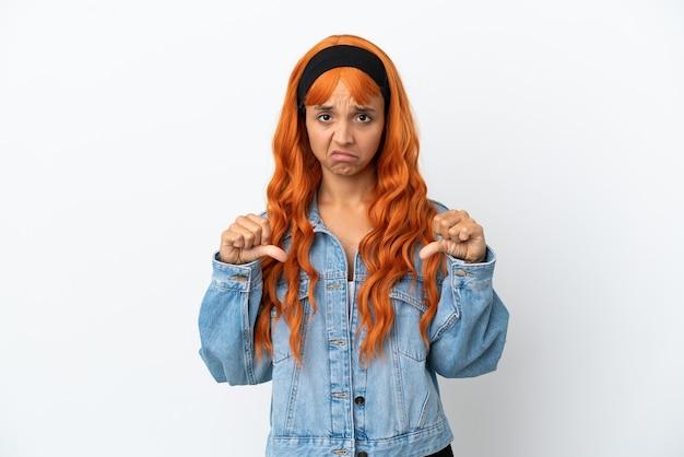Jeune femme aux cheveux orange isolé sur fond blanc montrant le pouce vers le bas avec deux mains