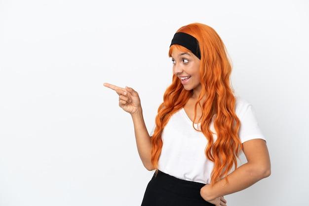 Jeune femme aux cheveux orange isolé sur fond blanc, pointant le doigt sur le côté et présentant un produit
