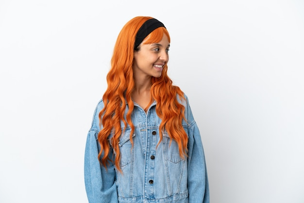Jeune femme aux cheveux orange isolé sur fond blanc regardant sur le côté et souriant