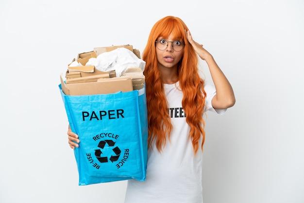 Jeune femme aux cheveux orange tenant un sac de recyclage plein de papier à recycler isolé sur fond blanc avec une expression de surprise