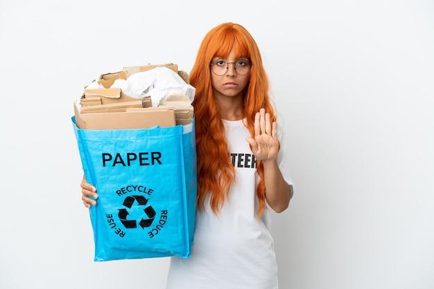 Jeune femme aux cheveux orange tenant un sac de recyclage plein de papier à recycler isolé sur fond blanc faisant un geste d'arrêt