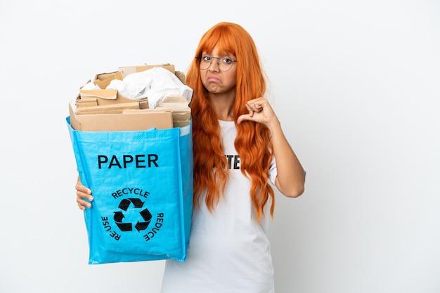 Jeune femme aux cheveux orange tenant un sac de recyclage plein de papier à recycler isolé sur fond blanc fier et satisfait de lui-même