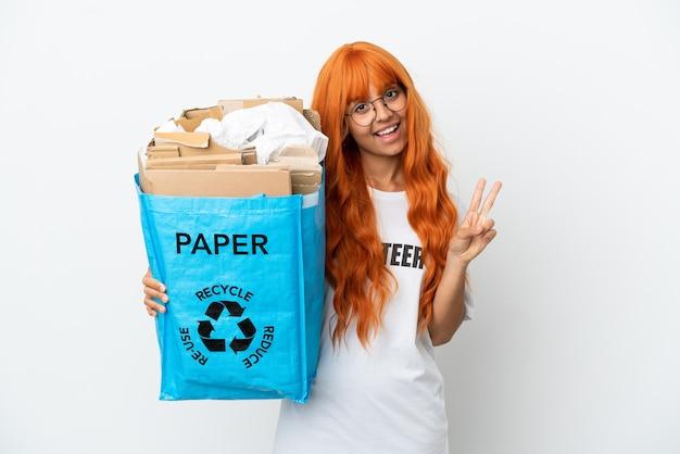 Jeune femme aux cheveux orange tenant un sac de recyclage plein de papier à recycler isolé sur fond blanc souriant et montrant le signe de la victoire