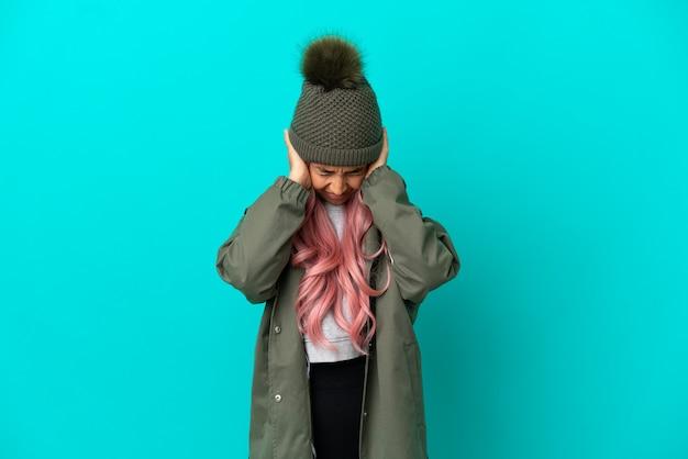 Jeune femme aux cheveux roses portant un manteau imperméable isolé sur fond bleu frustré et couvrant les oreilles