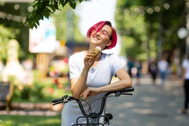 Jeune femme aux cheveux roses se promène dans le parc avec un vélo en train de manger de la glace en été. mode de transport environnemental