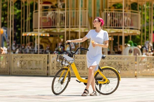 Jeune femme aux cheveux roses se promène dans le parc avec un vélo en train de manger de la glace en été.