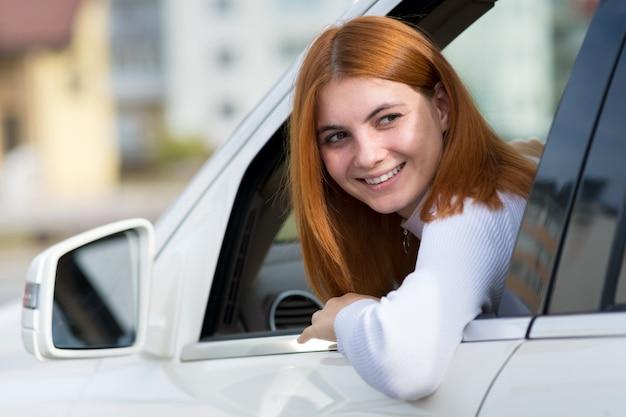 Jeune femme aux cheveux rouges au volant d'une voiture.
