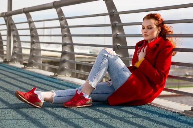 Une jeune femme aux cheveux rouges dans un manteau rouge et des baskets rouges est assise sur un pont sur un ensoleillé