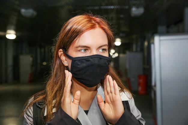 Une jeune femme aux cheveux rouges dans un passage pour piétons sombre ajuste un masque de protection noir