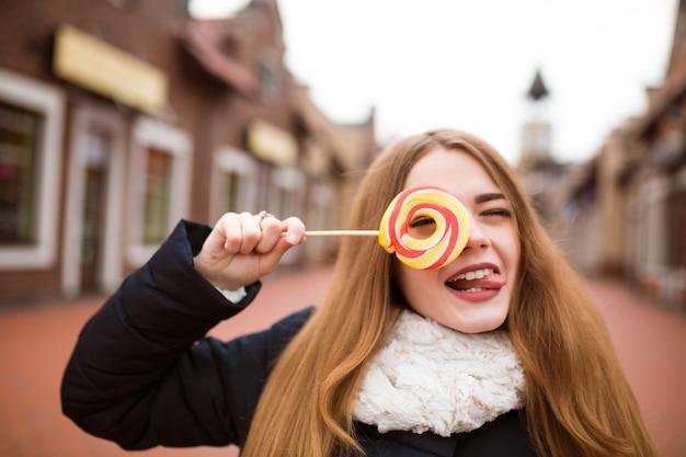 Jeune femme aux cheveux rouges drôle tenant des bonbons de noël colorés dans la rue