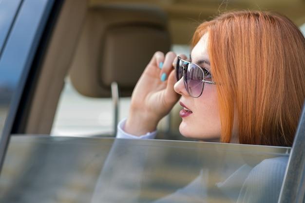 Jeune femme aux cheveux rouges et lunettes de soleil voyageant en voiture. passager regardant par la fenêtre arrière d'un taxi dans une ville.