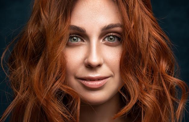 Jeune femme aux cheveux rouges ondulés montre la joie.