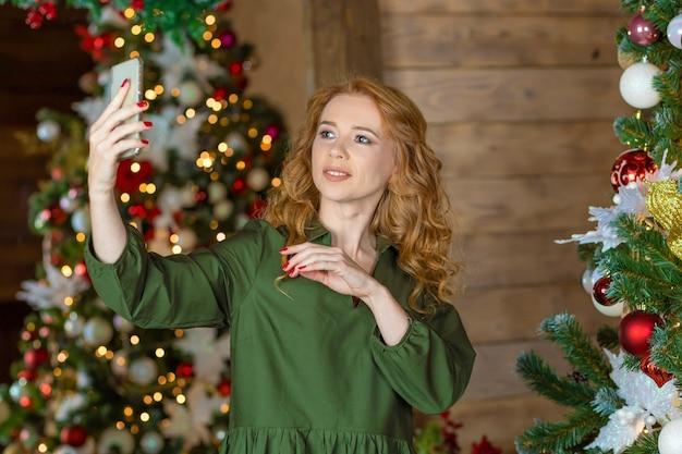Jeune femme aux cheveux rouges près de l'arbre de noël faisant selfie. fille au gingembre parlant en vidéo, faisant des photos sur smartphone, félicitant le nouvel an en ligne.