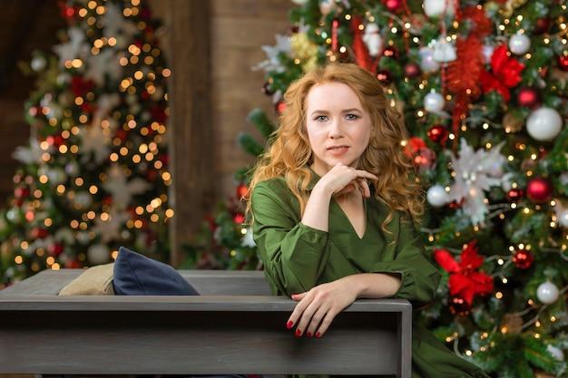 Jeune femme aux cheveux rouges près de l'arbre de noël. femme attendant le nouvel an à l'intérieur de la maison