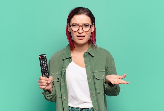 Jeune femme aux cheveux roux attrayante à la recherche en colère, agacée et frustrée crier wtf ou ce qui ne va pas avec vous et tenant une télécommande de télévision