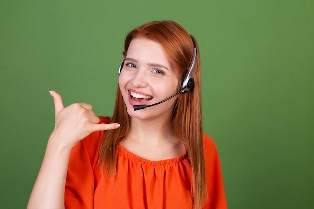 Jeune femme aux cheveux roux en blouse orange décontractée sur un mur vert responsable du centre d'appels, travailleur de la ligne d'assistance accueillant tous les appels sourire