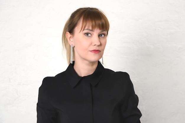 Jeune femme aux cheveux tirés en arrière et frange en robe noire à col rond contre le mur blanc.