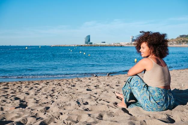 Jeune femme aux courbes afro à la plage de barcelone en été