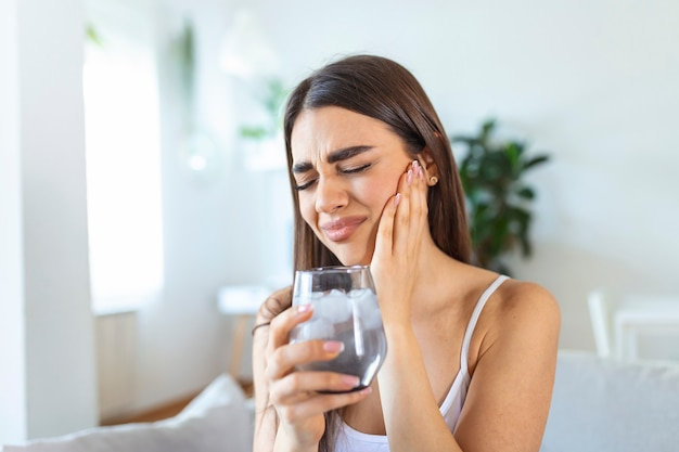 Jeune femme aux dents sensibles faisant mal et tenant un verre d'eau froide avec de la glace à la maison