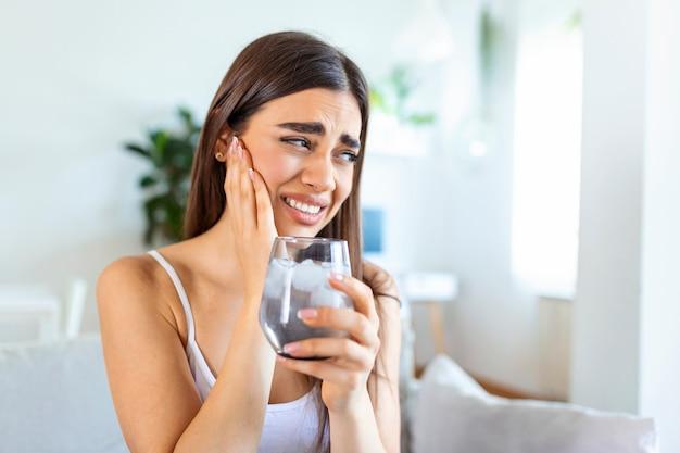 Jeune femme aux dents sensibles et main tenant un verre d'eau froide avec de la glace. concept de soins de santé. femme buvant une boisson froide, un verre plein de glaçons et ressent des maux de dents, de la douleur