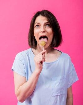 Jeune femme aux dents sensibles mangeant une sucette sucrée sur fond de couleur