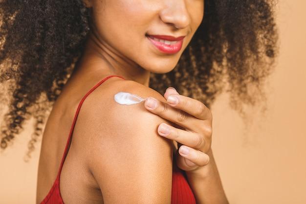 Jeune femme aux épaules nues debout sur beige appliquant la crème sur le corps souriant joyeux.