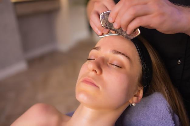 Jeune femme aux épaules nues utilisant un masseur de visage tout en se tenant isolée sur le fond marron et en détournant les yeux.