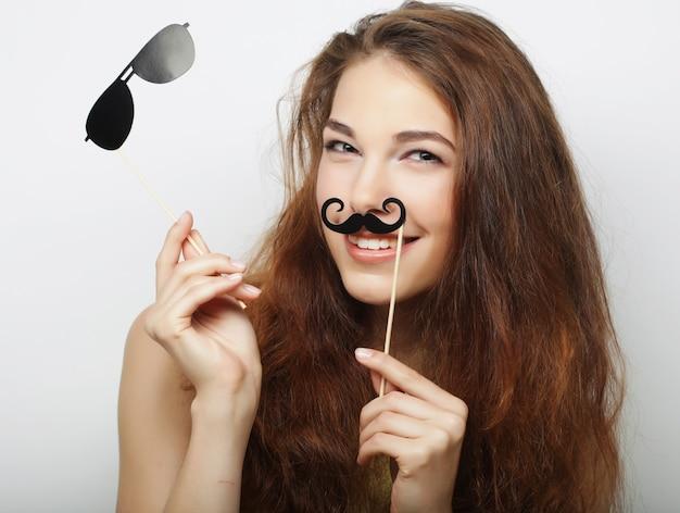 Jeune femme aux fausses moustaches. prêt pour la fête.