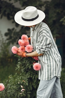 Jeune femme aux fleurs roses. dame au chapeau. fille dans un jardin.