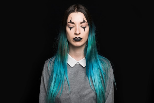 Jeune femme aux longs cheveux bleus debout en studio