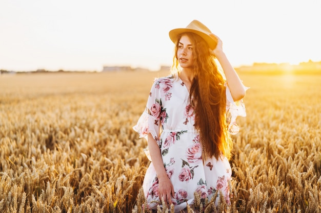Jeune femme aux longs cheveux bouclés et visage de taches de rousseur, au chapeau, en robe blanche claire avec imprimé floral, debout dans le champ de blé, posant