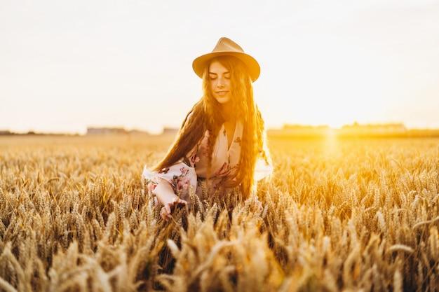 Jeune femme aux longs cheveux bouclés et visage de taches de rousseur, au chapeau, en robe blanche claire avec imprimé floral, debout dans le champ de blé